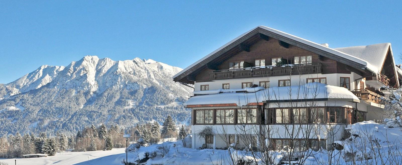 Hotel vor verschneitem Bergpanorama