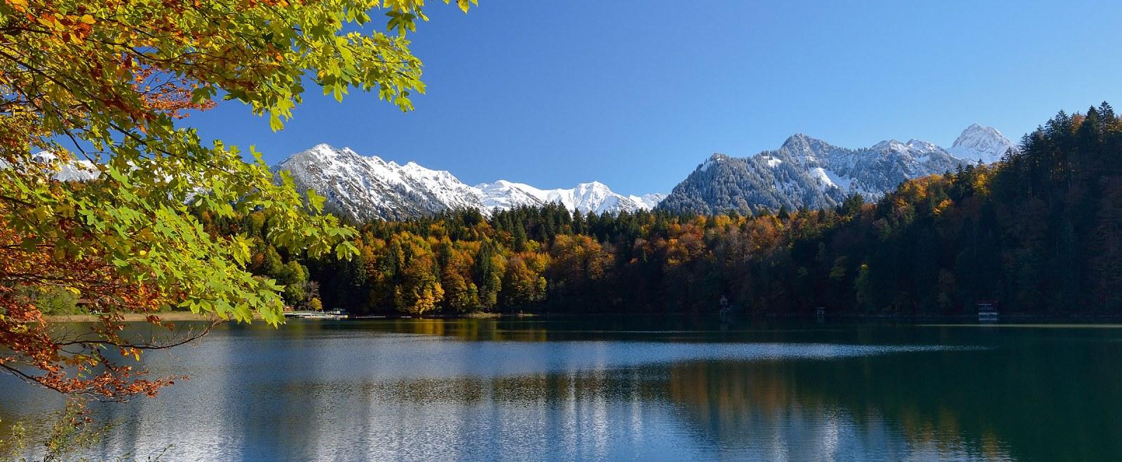 Freibergsee im Herbst mit verschneiten Bergen im Hintergrund